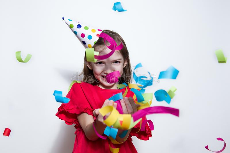 A child on a white background celebrates a bright event, wears a red dress and a cap. stock photo