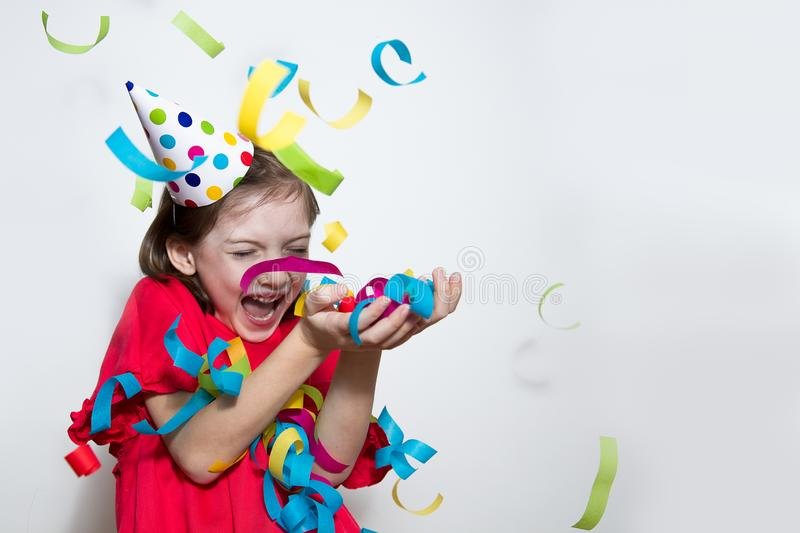 A child on a white background celebrates a bright event, wears a red dress and a cap. royalty free stock photos