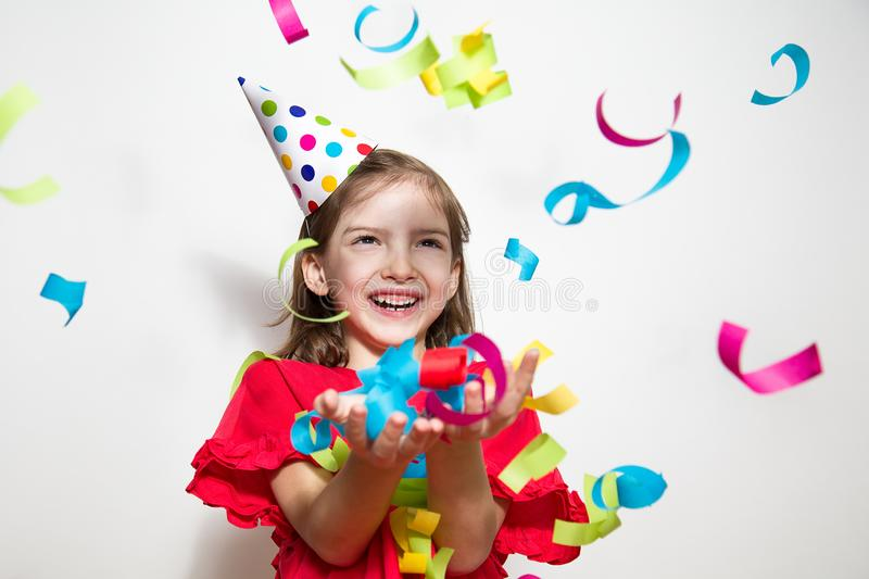 A child on a white background celebrates a bright event, wears a red dress and a cap. royalty free stock photo