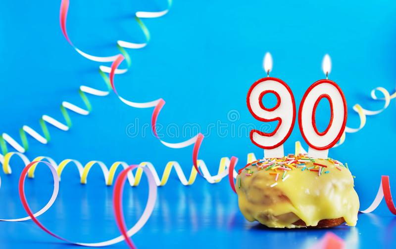 Birthday of ninety years. Cupcake with white burning candle in the form of number 90. Vivid blue background with copy space royalty free stock image