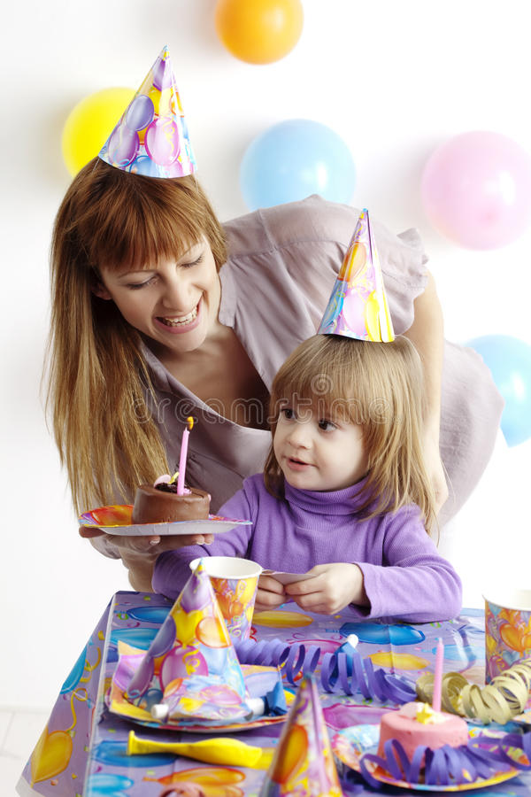Birthday party. Mother serving cake at childrens birthday party stock photography