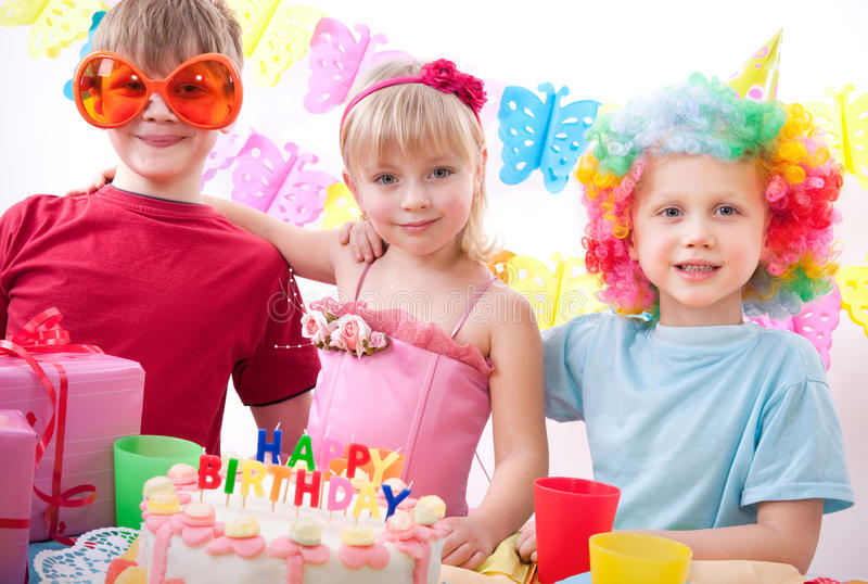 Birthday party. Three kids are happily posing during birthday party royalty free stock image