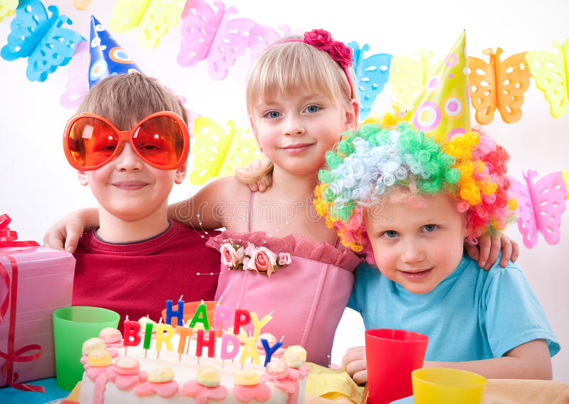 Birthday party. Three kids are happily posing during birthday party stock images