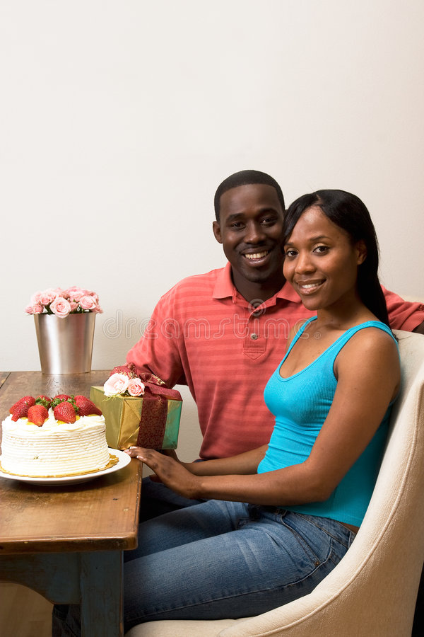 Birthday Party. Attractive smiling couple celebrating a birthday sitting at a table. On top of the table is a frosted cake with strawberries, a wrapped gift, and stock photo