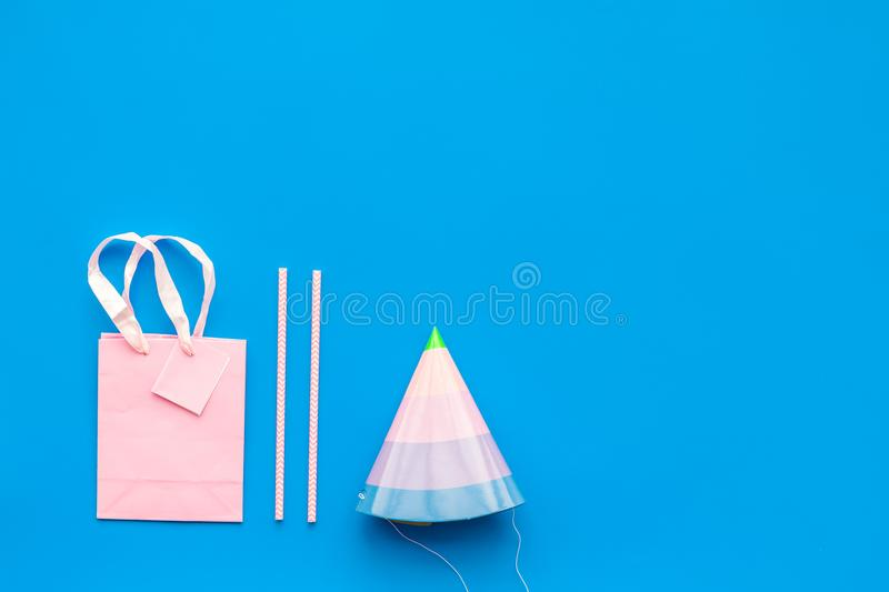 Birthday party accessories. Party hat, sweets, paper bag for gift on blue background top view copy space stock image