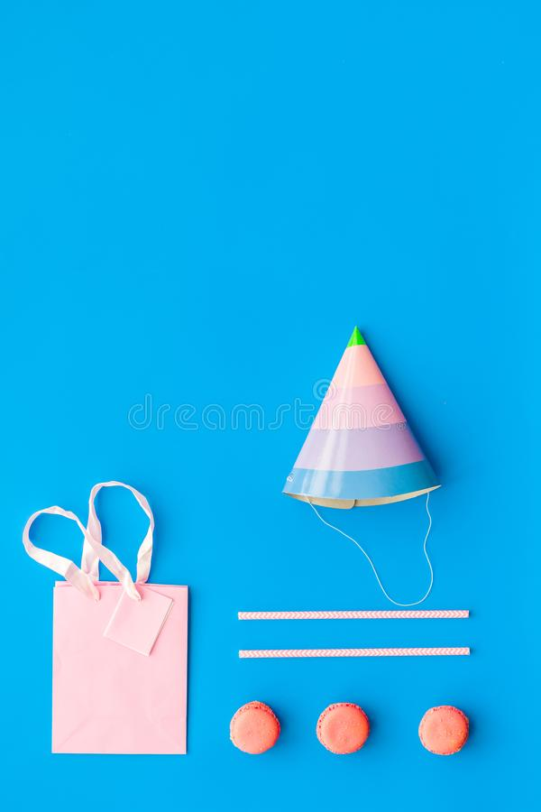 Birthday party accessories. Party hat, sweets, paper bag for gift on blue background top view copy space stock images