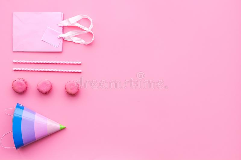 Birthday party accessories. Party hat, sweets, paper bag for gift on pink background top view copy space pattern royalty free stock photos