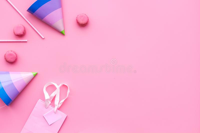 Birthday party accessories. Party hat, sweets, paper bag for gift on pink background top view copy space pattern stock photos