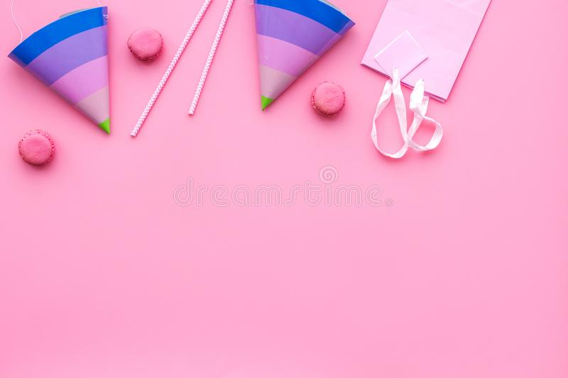 Birthday party accessories. Party hat, sweets, paper bag for gift on pink background top view copy space pattern royalty free stock image