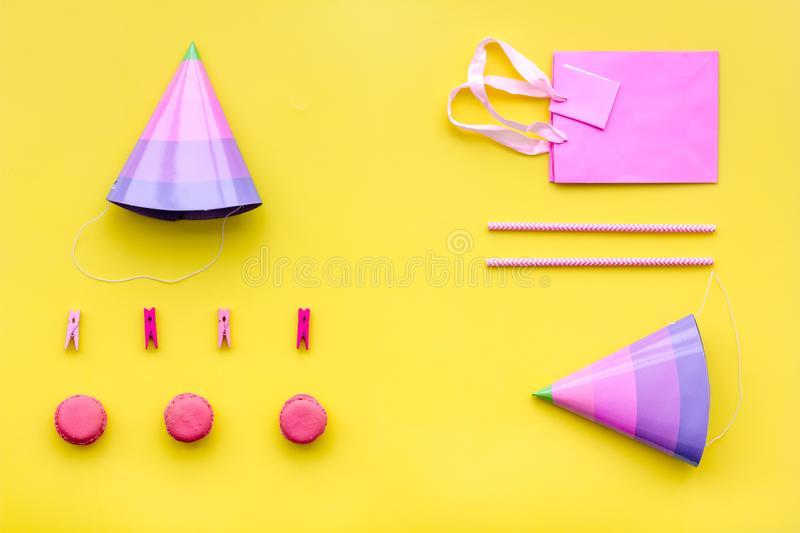Birthday party accessories. Party hat, sweets, paper bag for gift on yellow background top view copy mock up royalty free stock image