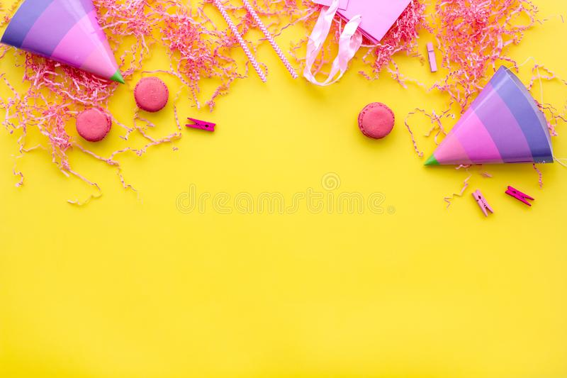 Birthday party accessories. Party hat, sweets, paper bag for gift on yellow background top view copy mock up stock image