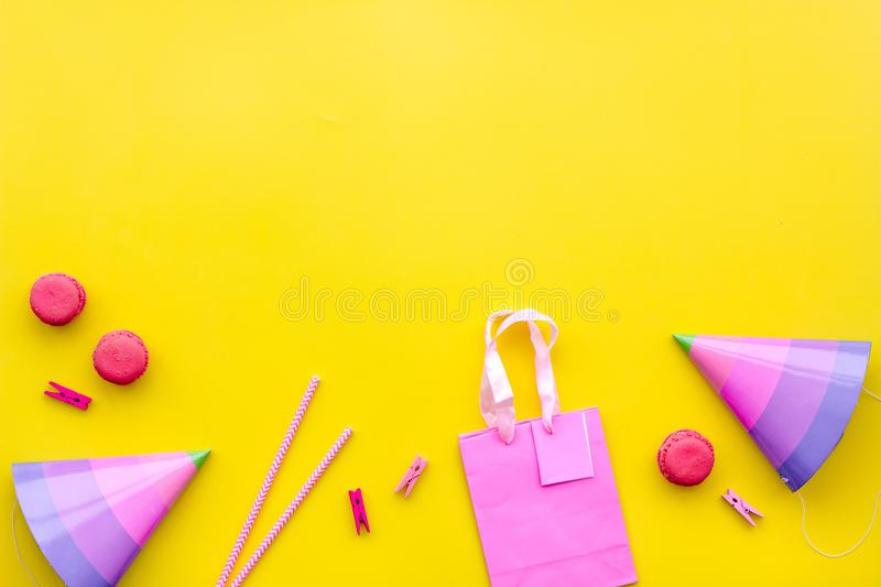 Birthday party accessories. Party hat, sweets, paper bag for gift on yellow background top view copy mock up stock images