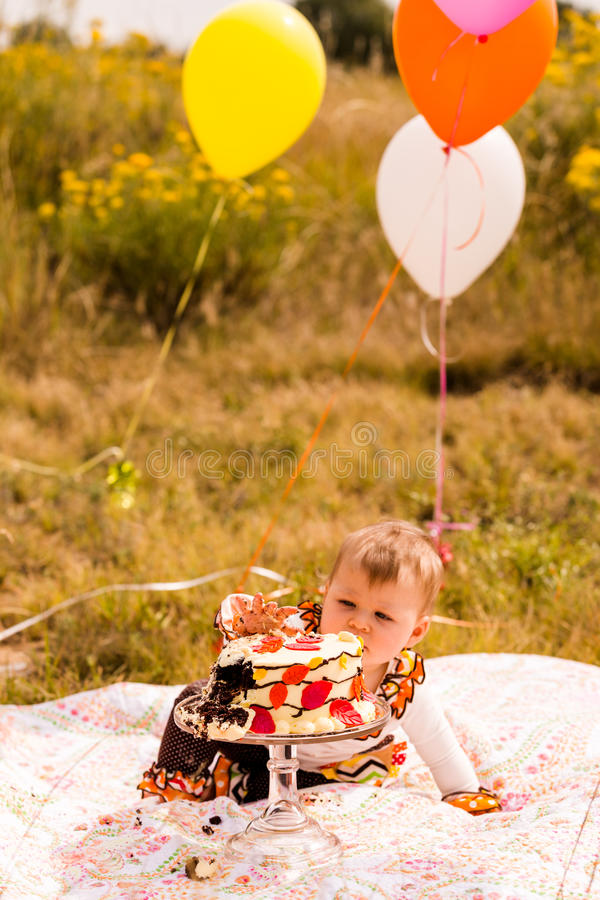 Birthday party. Baby girl celebrating her first bithday with gourmet cake and balloons royalty free stock images