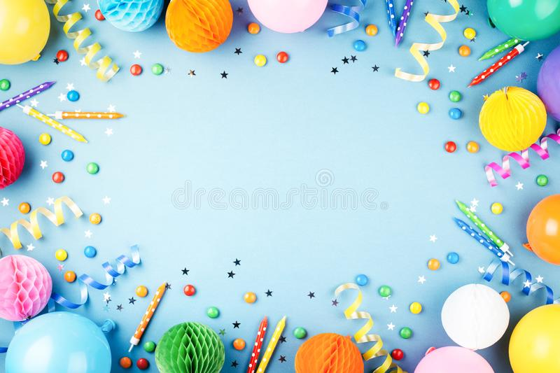 Birthday party background. On blue. Top view. Frame made of colorful serpentine, balloons, candles, candies and confetti royalty free stock images