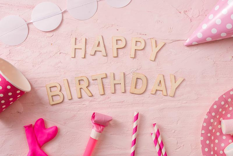 Birthday party background, border of confetti, sweets, lollipops and gift on pink surface, copy space, top view royalty free stock photo