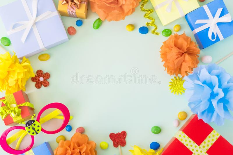 Birthday party background with festive decor, carnival glasses,. Ribbons, gift boxes, garland, pompoms on light background. Colorful celebration background royalty free stock photos