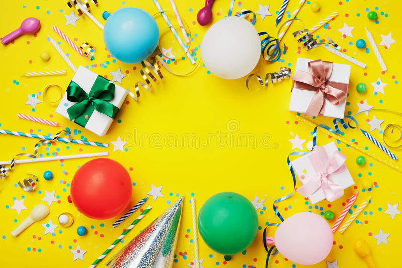 Birthday party background or frame with colorful balloon, gift, confetti, silver star, carnival cap, candy and streamer. Flat lay. Style. Holiday flyer with royalty free stock image