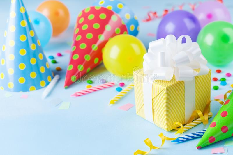 Birthday party background with gift box, colorful balloons, confetti, carnival cap and streamer. Holiday supplies on table. Birthday party background with gift royalty free stock photography