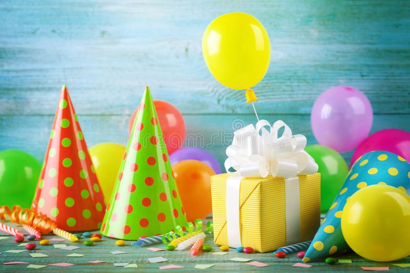 Birthday party background with gift box, colorful balloons, confetti, carnival cap and streamer. Holiday supplies on blue table. Birthday party background with stock photos