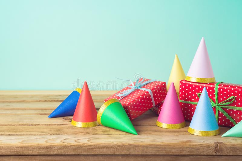 Birthday party background with gift boxes and party hats on wooden table. Birthday party  background with gift boxes and party hats on wooden table stock photos