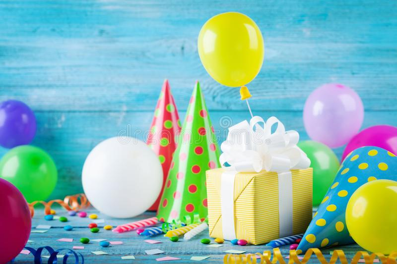 Birthday party background with gift or present box, colorful balloons, confetti, carnival cap and streamer. Holiday supplies. On blue table stock photos