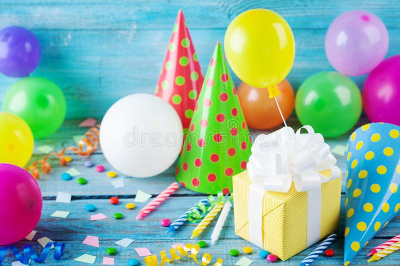 Birthday party background with gift or present box, colorful balloons, confetti, carnival cap and streamer. Holiday supplies. On blue table royalty free stock image