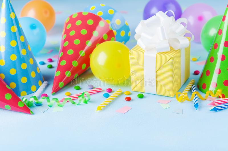 Birthday party background with gift or present box, colorful balloons, confetti, carnival cap and streamer. Holiday supplies. On blue table stock images