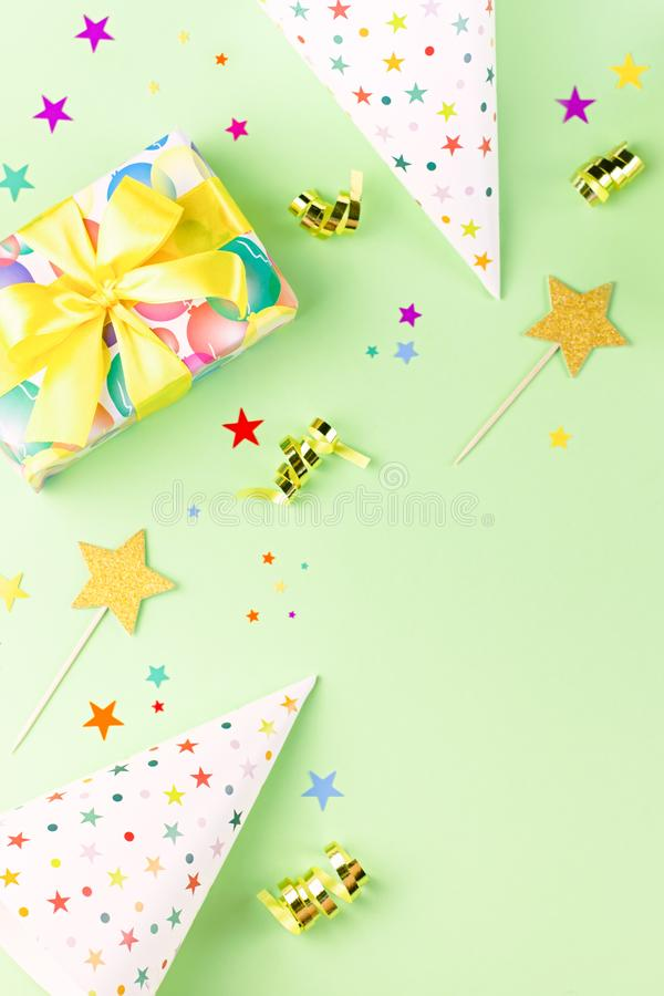 Birthday party background with wrapped gifts, confetti, party hats, decorations, top view royalty free stock photography