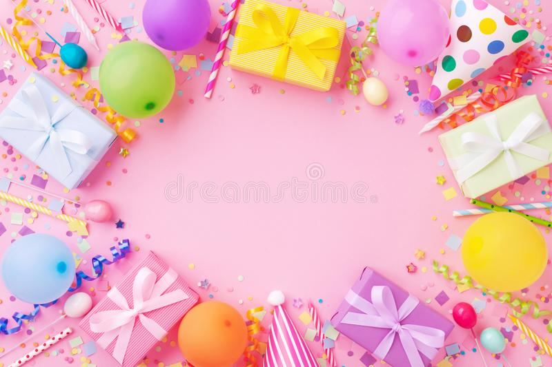 Birthday party banner or background with colorful balloons, carnival caps, gift boxes and confetti. Top view. Flat lay royalty free stock images