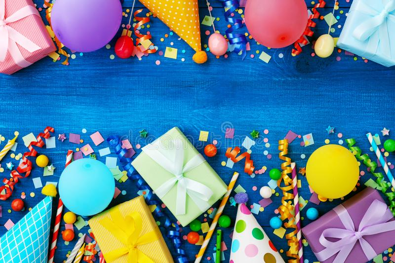 Birthday party banner or background with colorful carnival caps, balloons, gift or present boxes and confetti. Top view.  stock photos