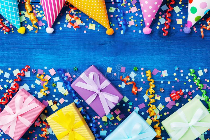 Birthday party banner or background with colorful carnival caps, gift boxes and confetti. Top view. Birthday party banner or background with colorful carnival royalty free stock photo