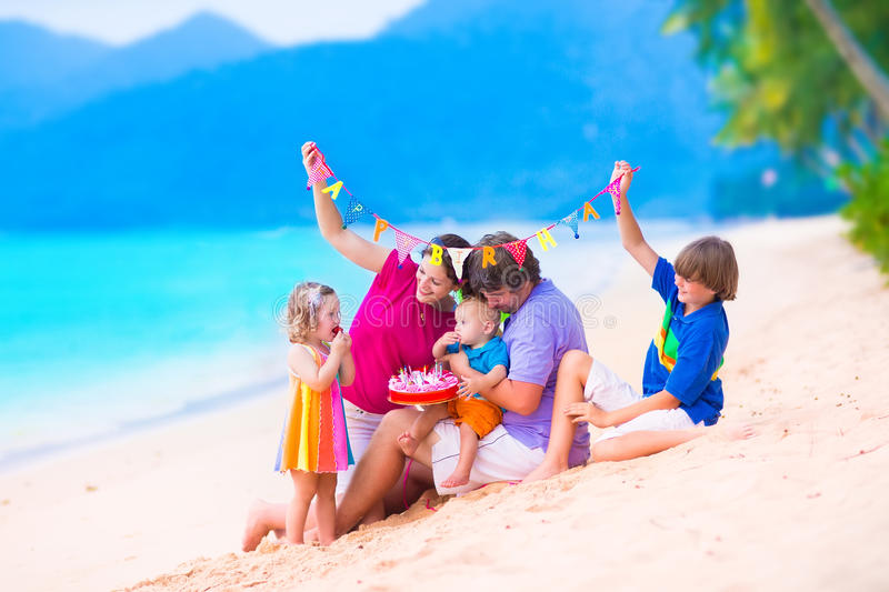 Birthday party at a beach. Happy young family with three children celebratin birthday party at a tropical beach. Parents with baby, teenager boy and cute little royalty free stock photography