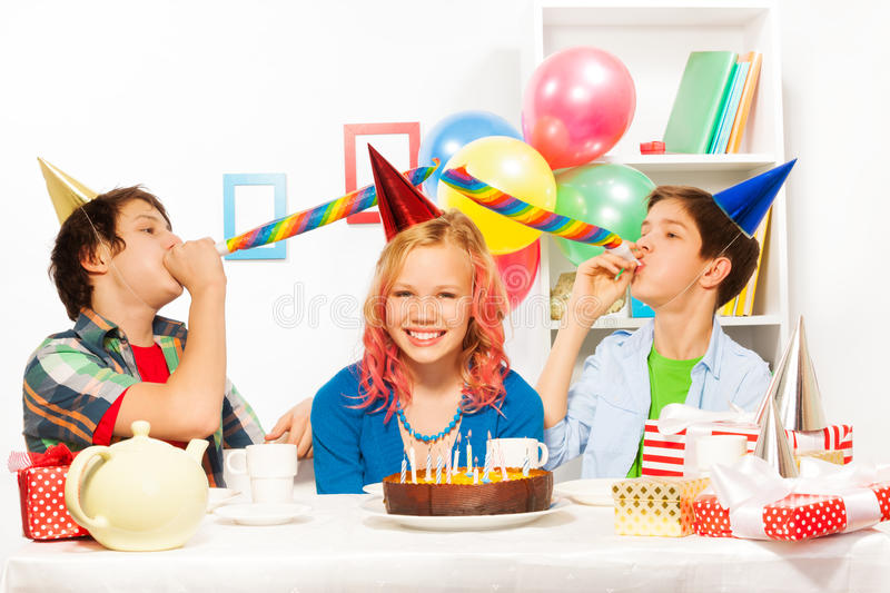 Birthday party with boys blow noisemaker horns royalty free stock photography