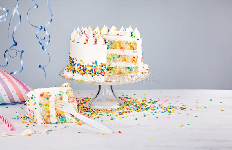 Birthday Party Cake with Sprinkles. White buttercream confetti Birthday cake and slice with colorful sprinkles over a gray background stock photos