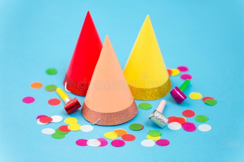 Birthday party caps, horns and colorful confetti. Celebration and decoration concept - three birthday party caps, horns and colorful confetti on blue background stock image