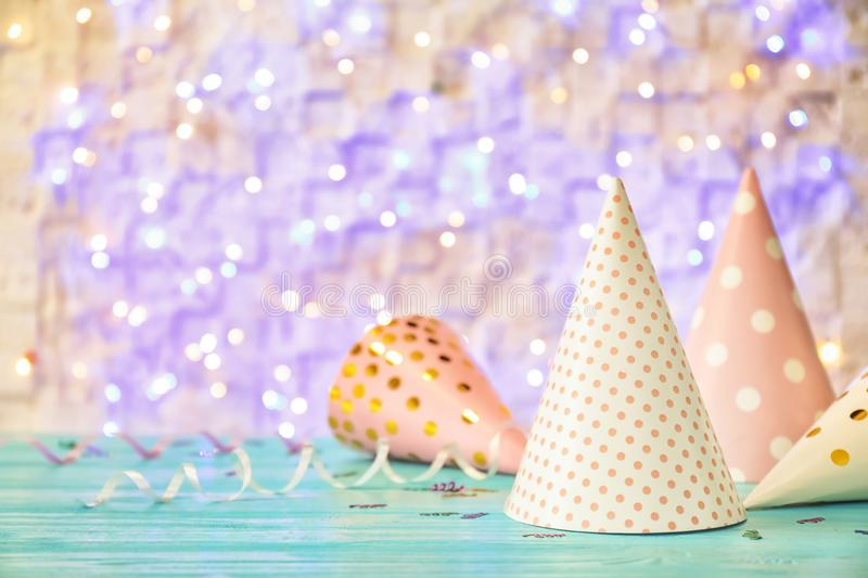 Birthday party caps on table against lights royalty free stock photos