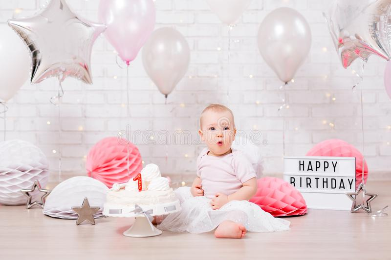 Birthday party concept - amazed little girl with cake over brick wall background with lights and balloons royalty free stock photo