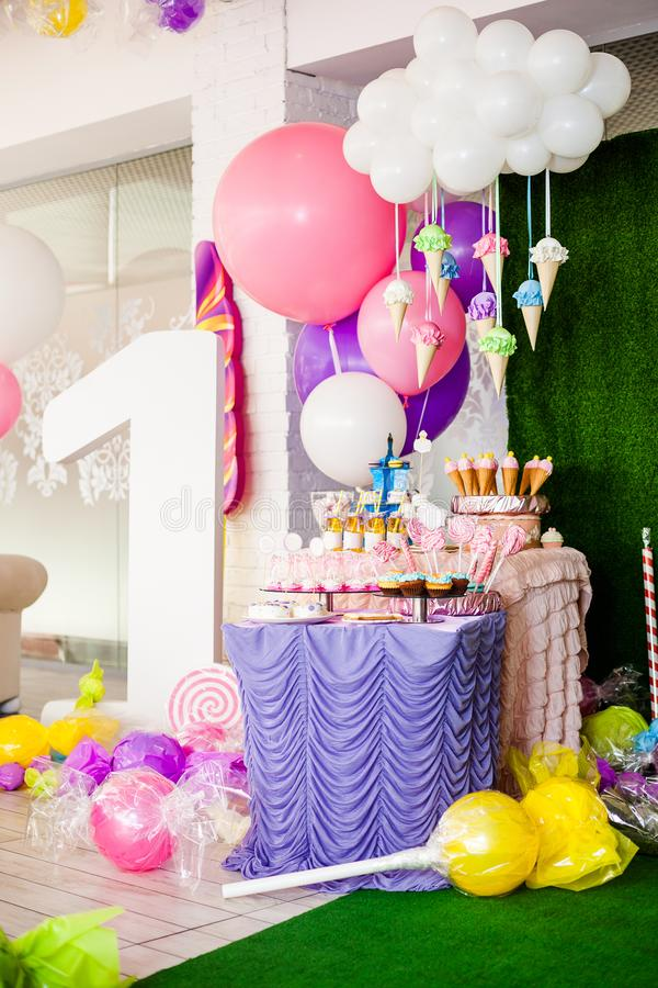 Birthday party concept, candy bar for children. Huge number one, table with sweets and desserts, cloud from balloons and ice-cream stock photography