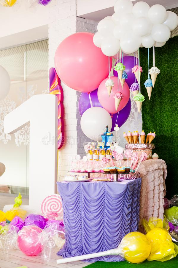Birthday party concept, candy bar for children. Huge number one, table with sweets and desserts, cloud from balloons and ice-cream. S, a lot of colored balloons royalty free stock image