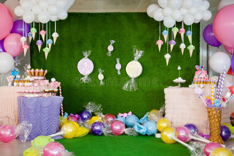 Birthday party concept, decorations for sweet party. Huge number one, table with sweets and desserts, cloud from balloons and ice-. Creams, a lot of colored royalty free stock photos
