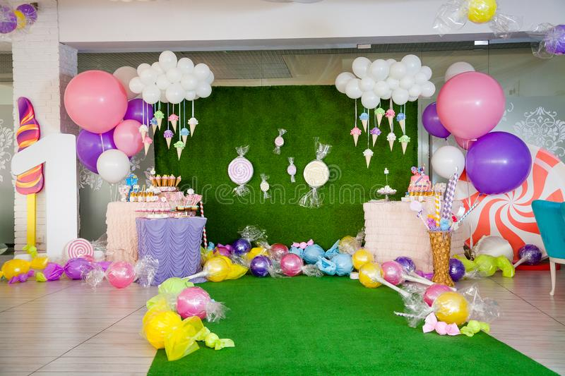 Birthday party concept, decorations for sweet party. Huge number one, table with sweets and desserts, cloud from balloons and ice-. Creams, a lot of colored stock image