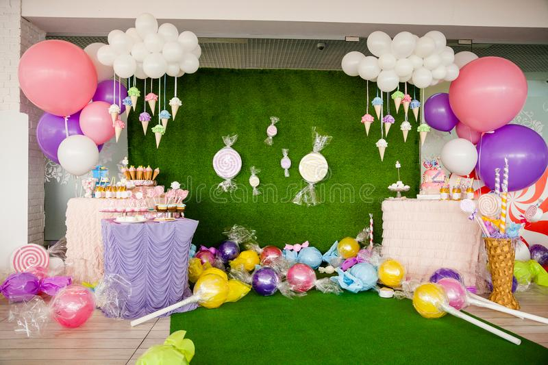 Birthday party concept, decorations for sweet party. Huge number one, table with sweets and desserts, cloud from balloons and ice-. Creams, a lot of colored stock images