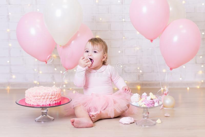 birthday party concept - funny little girl eating cake over brick wall background with lights and balloons royalty free stock photos