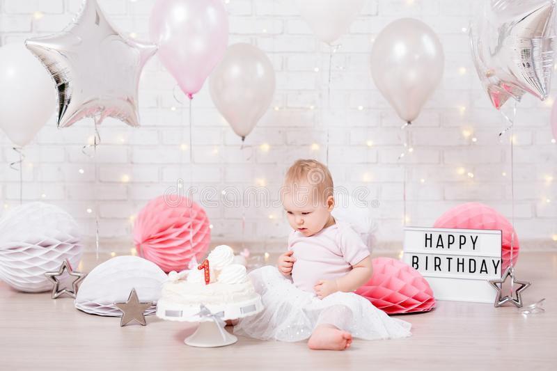 Birthday party concept - little girl with cake over brick wall background with lights and balloons stock photos