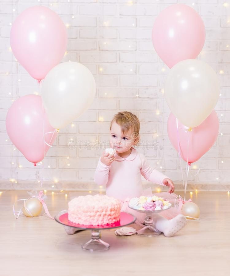 Birthday party concept - little girl eating cake over brick wall royalty free stock images