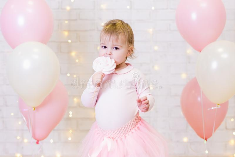 Birthday party concept - portrait of little girl eating sweets o. Birthday party concept - portrait of cute little girl eating sweets over brick wall background royalty free stock photography