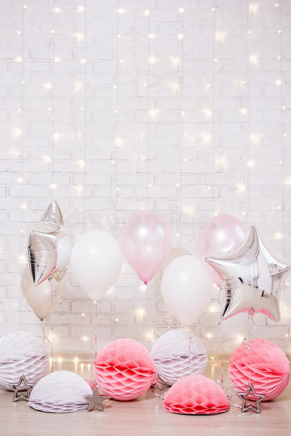 Birthday party decoration - air balloons, stars, paper balls and copy space over brick wall with lights stock photography