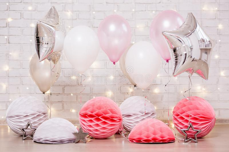 Birthday party decoration - close up of air balloons, stars and paper balls over brick wall with lights. Birthday party decoration - close up of colorful air stock images