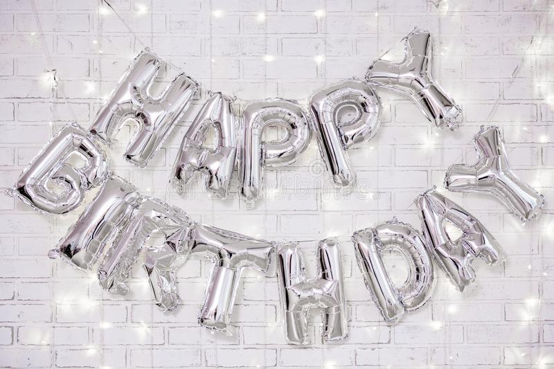 Birthday party decoration - happy birthday letters air balloons over brick wall with lights. Birthday party decoration - happy birthday letters air balloons over stock images