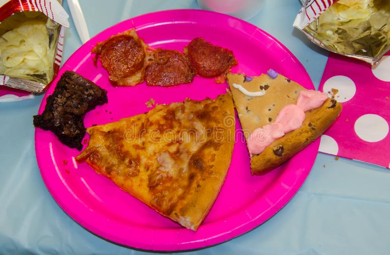 Birthday party food with one bite taken from assorted treats including pizza, chips, cookie cake and brownies. royalty free stock photo